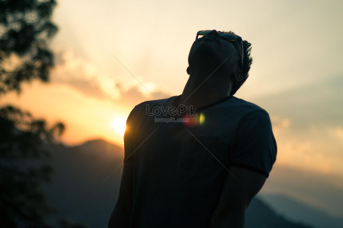 夕陽下登山者的背影圖片