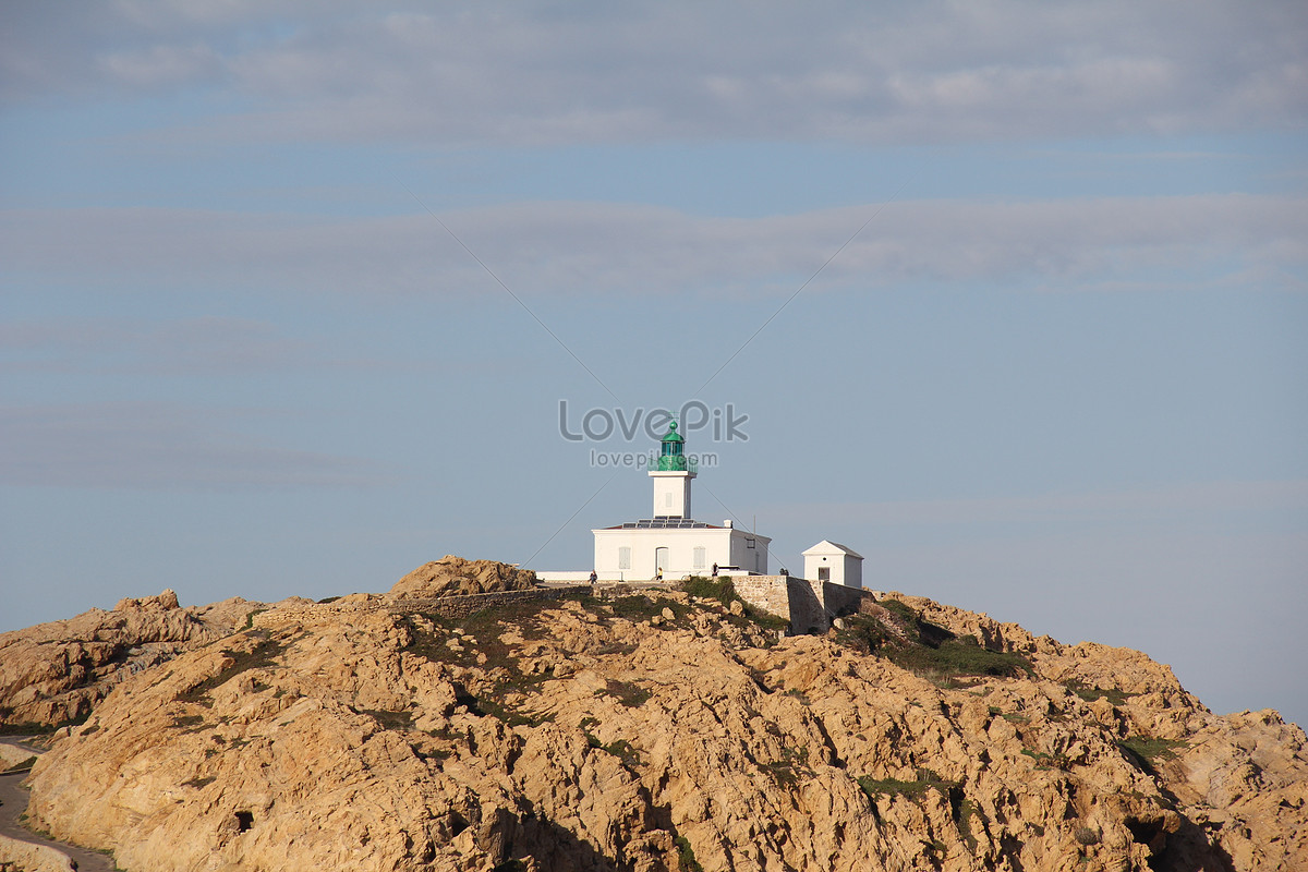 A lighthouse on a rock cliff photo image_picture free
