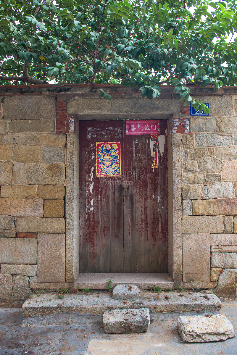 Stone Walls And Red Wooden Doors In The Ancient House Photo